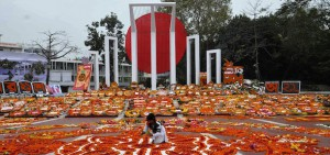 Bangladesh's Language Movement martyrs monument is covered with floral tributes as a Bangladeshi youth adds the finishing touches to a display in Dhaka on February 21, 2011, to pay homage to the martyrs of the 1952 Bengali Language Movement. Tens of thousands of mourners walking barefoot thronged the memorial for the annual traditional remembrance of those killed when police fired on campaigners on this day in 1952, who were demanding Bengali be declared as one of the state languages of what was then Pakistan.  AFP PHOTO/ STRINGER (Photo credit should read STRINGER/AFP/Getty Images)